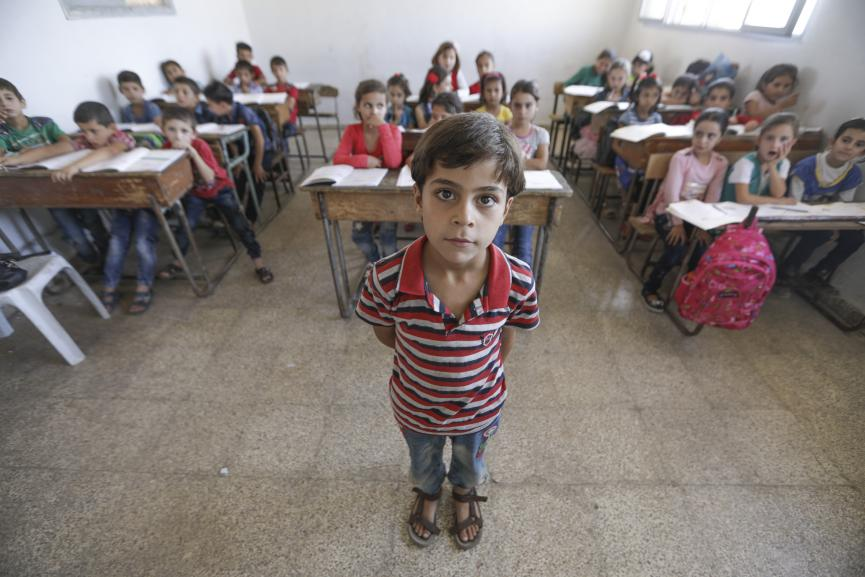 A boy stands in the front of a classroom, Syrian Arab Republic