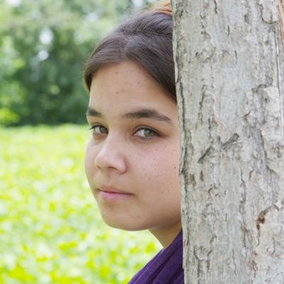 A young girl peering from behind a tree