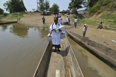 A health worker stands in a long canoe