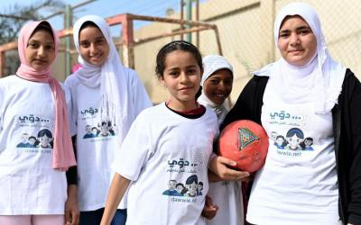 A group of girls standing together holding a basketball