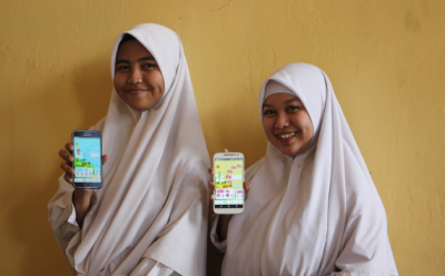 Two Indonesian girls holding up their mobile phones
