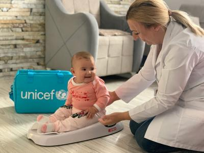 Unicef health nurse kneeling on the floor with a baby on a weighing scales
