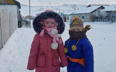 Two children wrapped up in warm winter clothes with snow on the ground around them