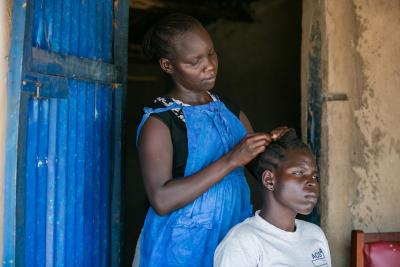 A teenage girl braids a girl's hair, Uganda
