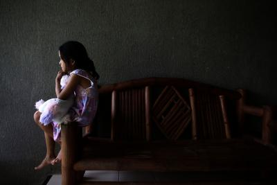 An 8-year-old girl clutches a stuffed toy while sitting on the arm of a bench at a shelter in her home country..