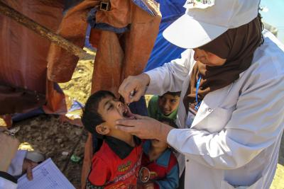A young boy is delivered an oral vaccine by a standing health worker
