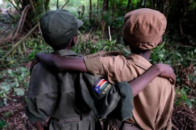 Two child soldiers in South Sudan stand with their backs to the camera, arms wrapped around each other, in 2018.
