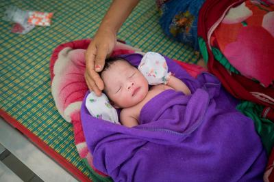 A mother touches her newborn baby, Cambodia.