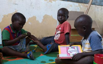 A group of young children sit playing with locally made toys in an Early Childhood Develoment Centre in Uganda