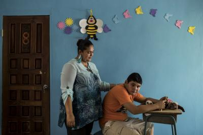 In Honduras, a fourteen-year-old boy sits at home as his mother places her palm on his back in comfort.