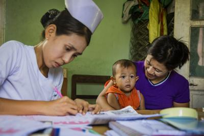 A nurse in Myanmar registers a baby, sitting on Mom's lap, for a birth certificate in 2018.