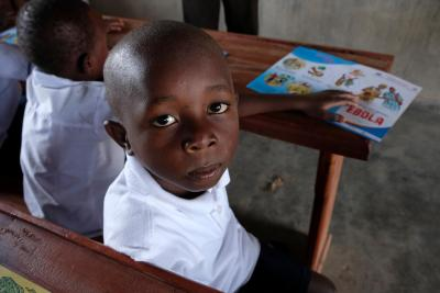 Democratic Republic of the Congo. A boy sits at his desk in a classroom.