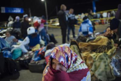 A young Venezuelan woman sits fully covered in a blanket, waiting to continue her journey at Rumichaca, on the border of Ecuador and Colombia, in 2018.