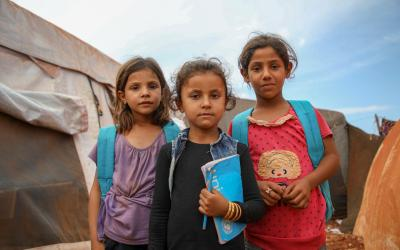 Three girls in a refugee camp holding UNICEF books and schoolbags