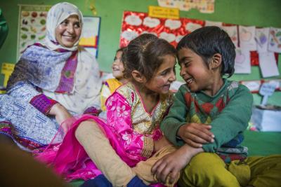 A community worker sits smiling behind two young children playing at an education centre in Jammu and Kashmir, 2018.