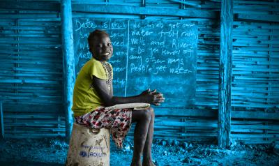 A girl sits in front of a chalkboard, South Sudan