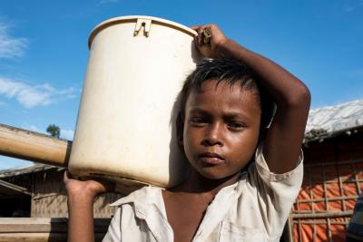 Bangladesh. A small boy carries a bucket at a refugee camp.