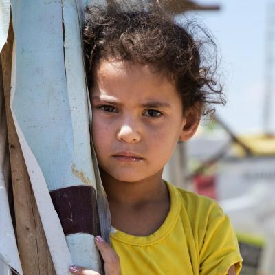 A child refugee stands at a shelter.