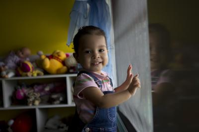 A little girl orphaned by her mother stands, smiling, with her hands on an orphanage window in Panama in 2012.