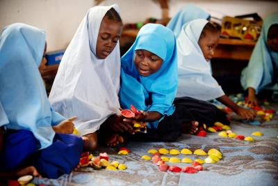 Schoolgirls sitting on the ground with educational toys