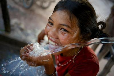 A girl laughs playfully while drinking water at a water point in Adone village of Ta Oi district, Saravane province, Lao PDR.