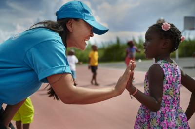 A UNICEF staff member gives a high five to a young girl