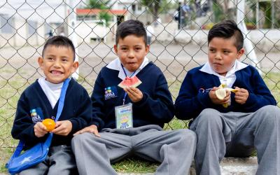 Three boys in school uniforms sitting and eating