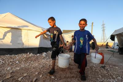 On 24 September 2019 in Idlib in the Syrian Arab Republic, children carry water containers from a tanker to take into the displaced camp near the town of Taftanaz.