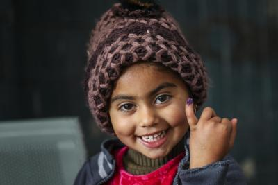 A smiling four year-old Pakistani girl shows off the ink mark on her little finger to confirm she was vaccinated against polio.