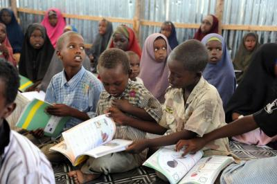 Primary school studens in Somalia sitting on benches with text books on their laps