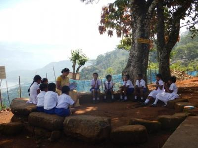 A teacher sitting with young students in school uniforms under trees