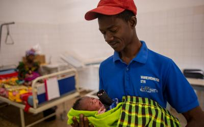 A man in a hospital holding his new-born baby