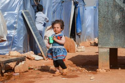 Syria. A girl stands outside a tent at a refugee camp.