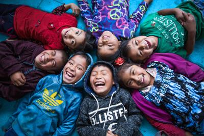 Girls and boys lie on the floor, heads together, laughing, in Guatemala in 2019.