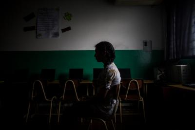 A girls sits in a classroom in El Salvador