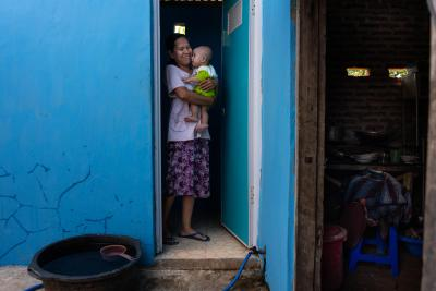 A mother holding a child at a toilet doorway