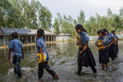 School children walking through flood waters