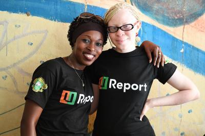 Two smiling women wearing U-Report t-shirts
