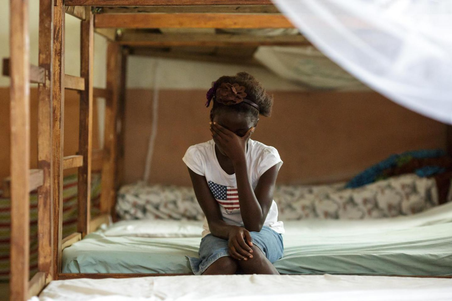 A girl sits on a bed with her head in her hand, Sierra Leone