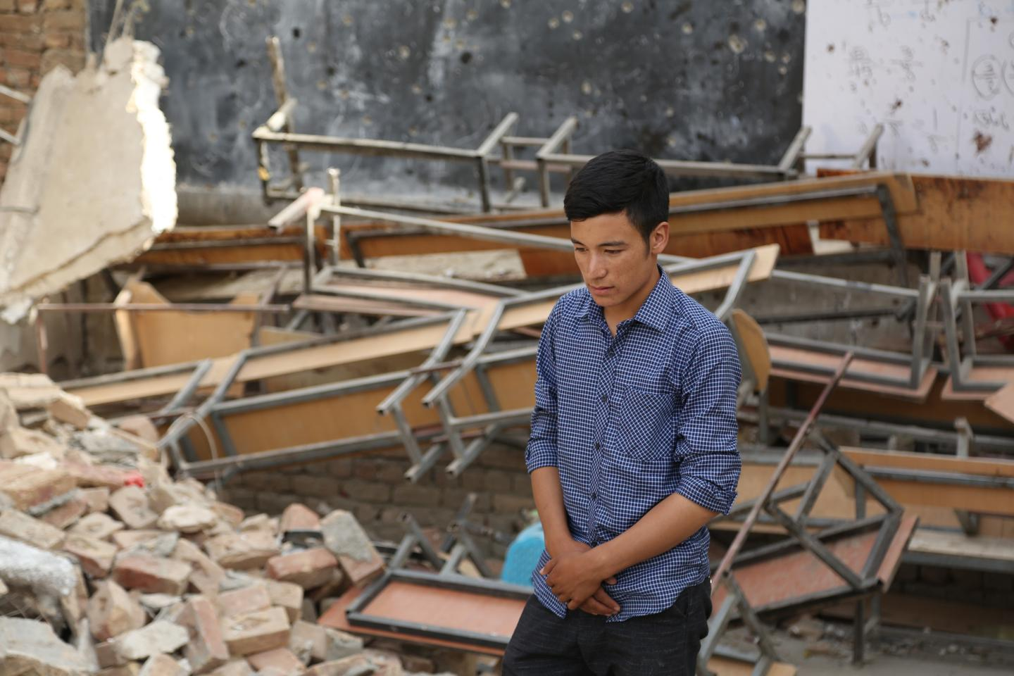 A boy stands among rubble, Afghanistan