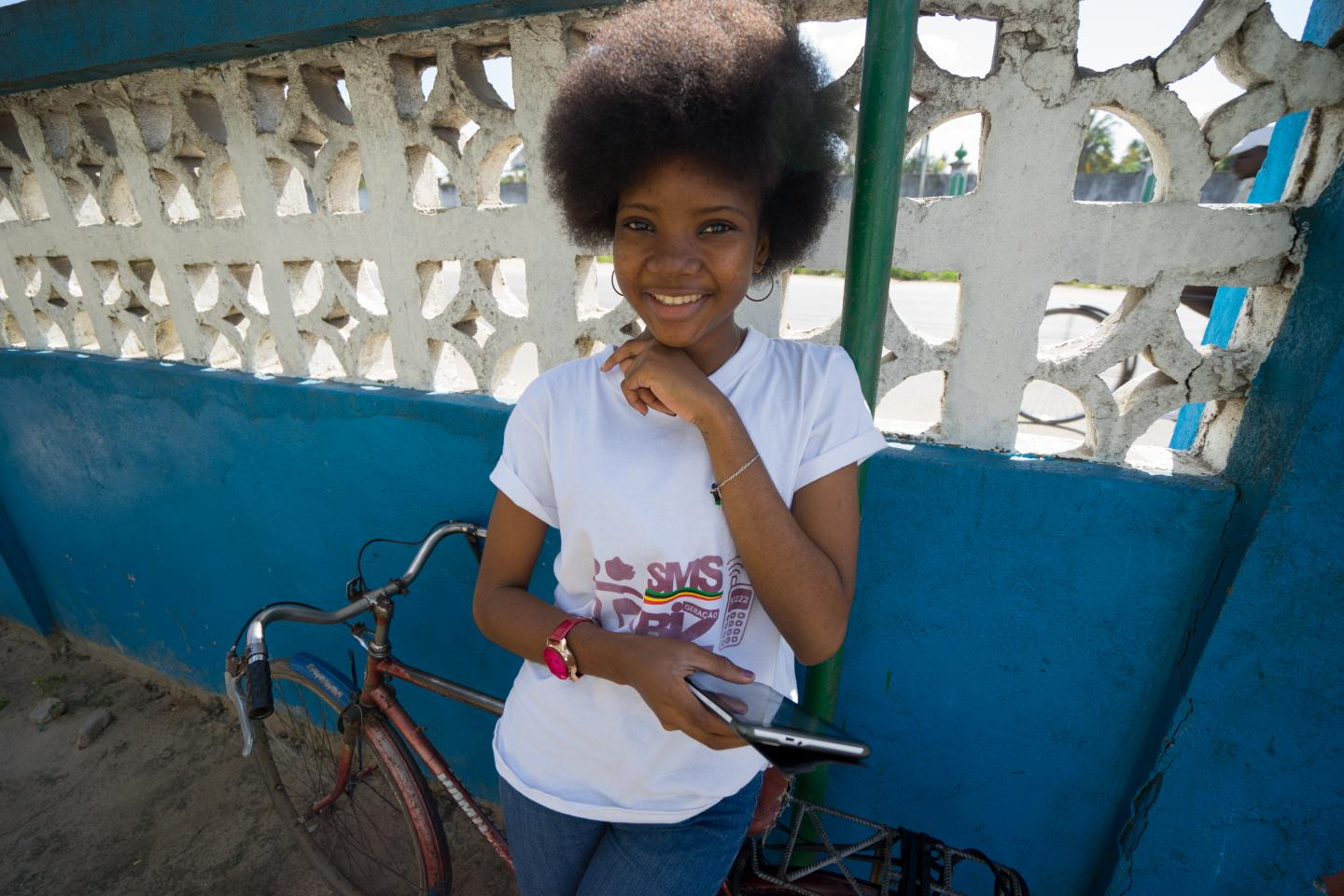 A teenage girl holds a mobile phone and smiles, Mozambique