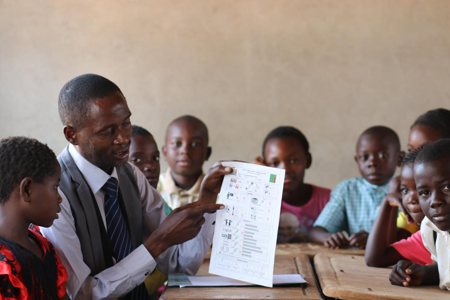 ata for better quality education: a volunteer shows school profile cards to students in a classroom.