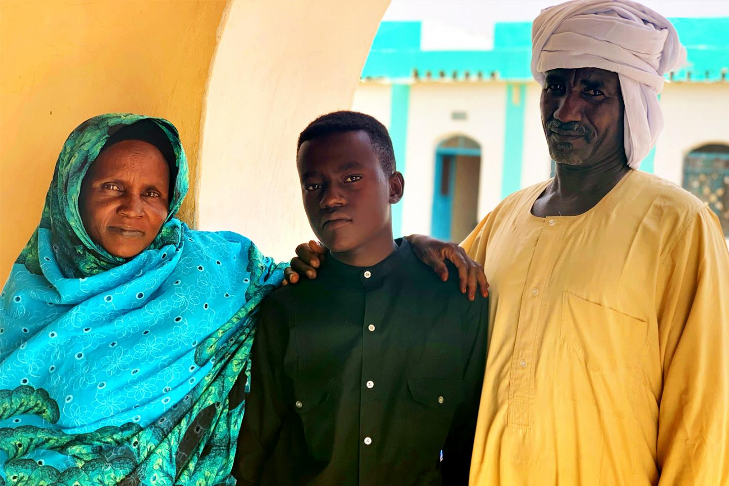 Sudan. A boy stands with his family.