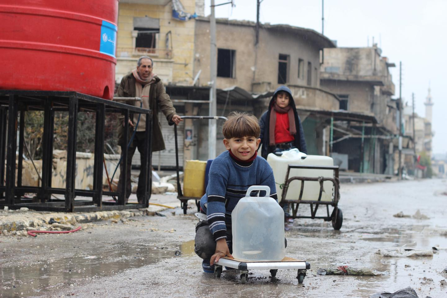 Families collect water from a UNICEF-supported water point in Shakoor neighbourhood, in east Aleppo City in the Syrian Arab Republic.