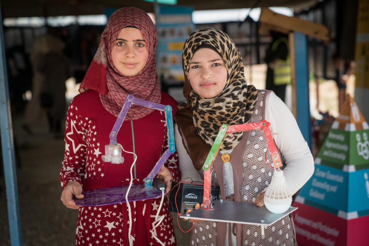 Two young women in headscarves stand together and hold their invention