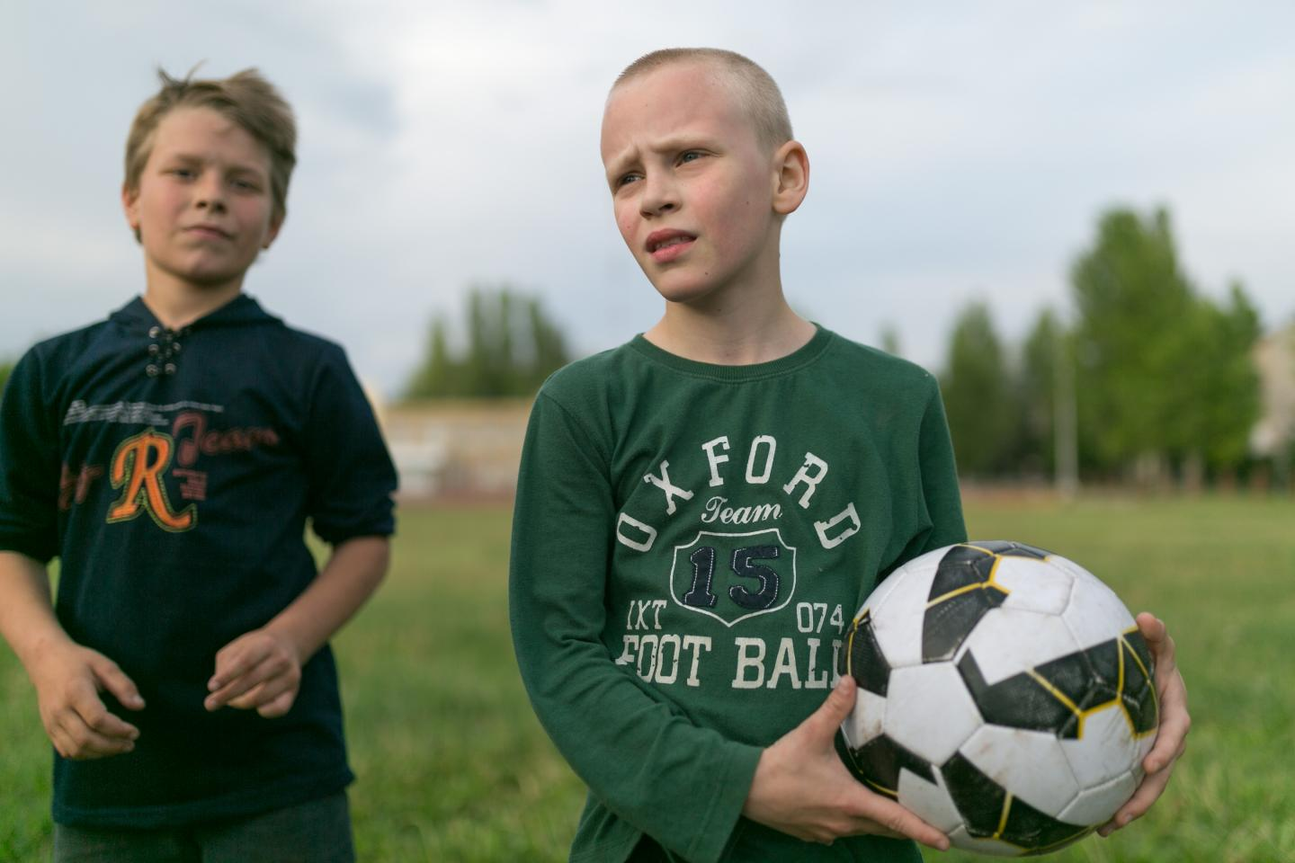 Two boys stand on a football field, Ukraine