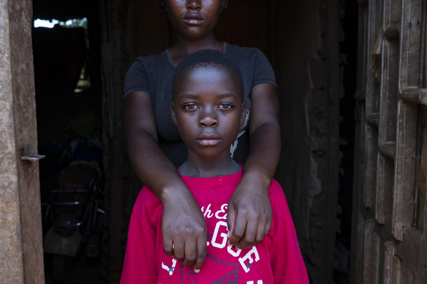 A girl wraps her arms around her sister, Democratic Republic of Congo