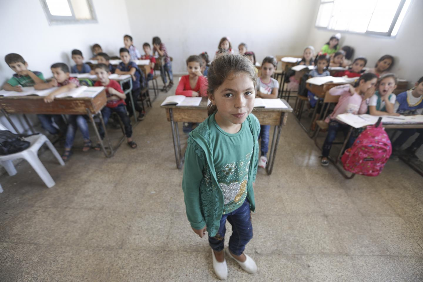 A girl stands at the front of the classroom, Idlib