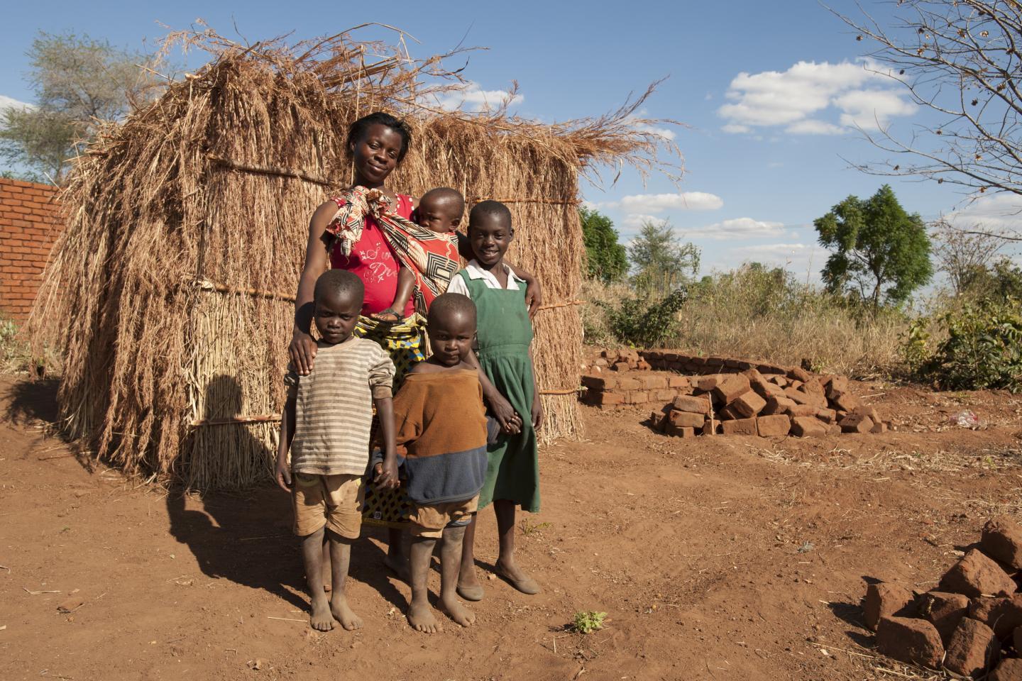 Alinafe and her family stand outside their only shelter, made from the husks of the maize plant in Balaka District in Malawi.