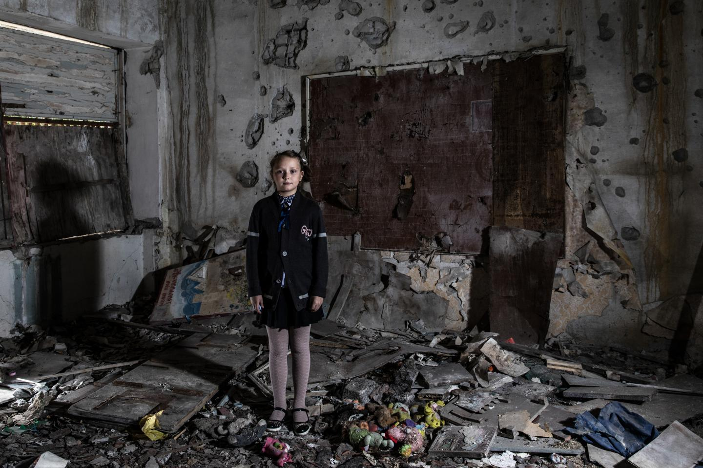Children under attack. A girl stands in a damaged classroom in eastern Ukraine.